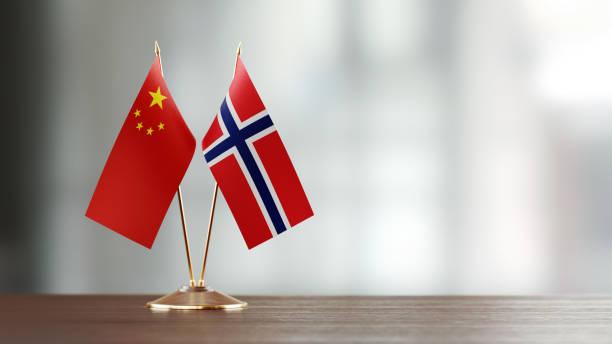 chinesische und norwegische flagge paar auf einem schreibtisch über defokussierten hintergrund - norwegen fahne stock-fotos und bilder