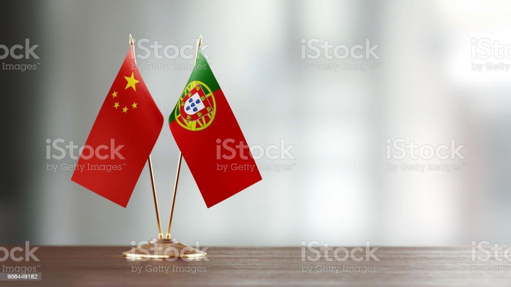 Par de la bandera China y portuguesa en un escritorio sobre fondo Defocused - foto de stock
