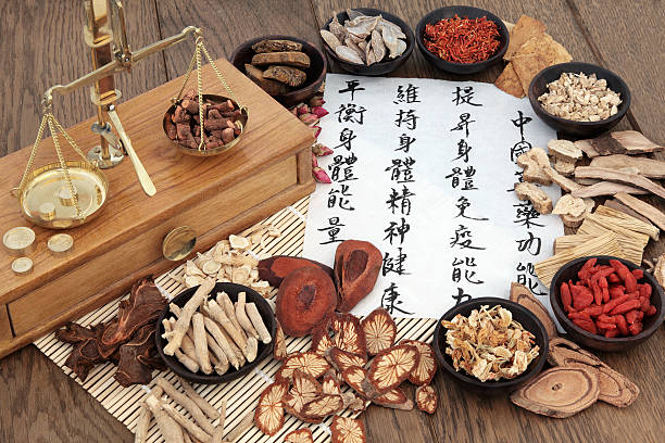 Chinese Apothecary Herbs Chinese herbal medicine with herb ingredients, scales and calligraphy on rice paper. Translation reads as chinese herbal medicine as increasing the bodys ability to maintain body and spirit health and balance energy. chinese herbal medicine stock pictures, royalty-free photos & images