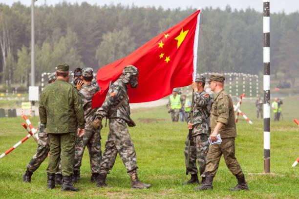 kinesisk armésoldat i en kemisk skyddsdräkt mot bakgrund av flaggan av folkets armé i kina - chinese military bildbanksfoton och bilder