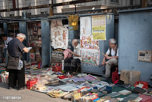 Beijing, China- June 10 2018: Chinese  asian man reading and selling antique books at Panjiayuan flea  antique Market in Beijing China.
