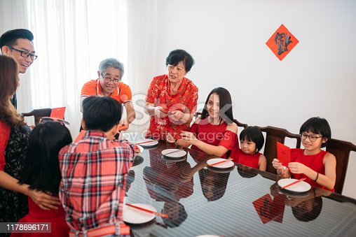 Image of Chinese Asian senior elders giving red packet or Angpow to younger generation during Chinese New Year lunch.