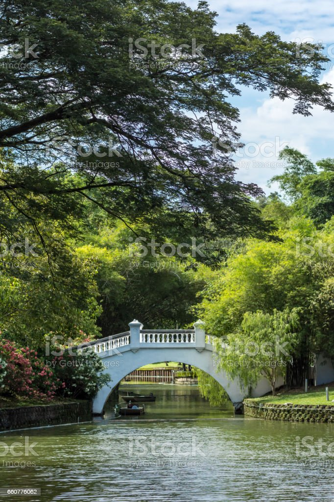 Chinese asian style concrete white footbridge over river in public oriental gardens on sunny day. stock photo