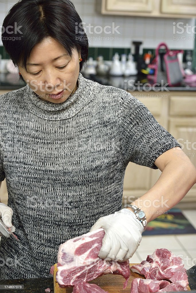 Chinese Asian woman cooking in her kitchen royalty-free stock photo
