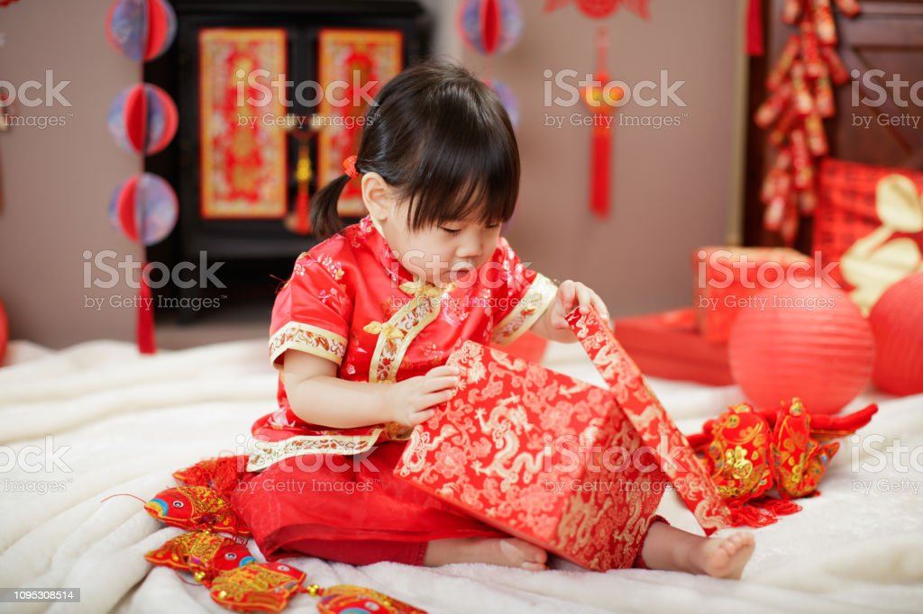 Chinese baby girl  traditional dressing up celebrate Chinese new year open gift box stock photo