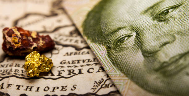 Chinese banknote and a gold nugget and rare earth metal on map of Africa stock photo