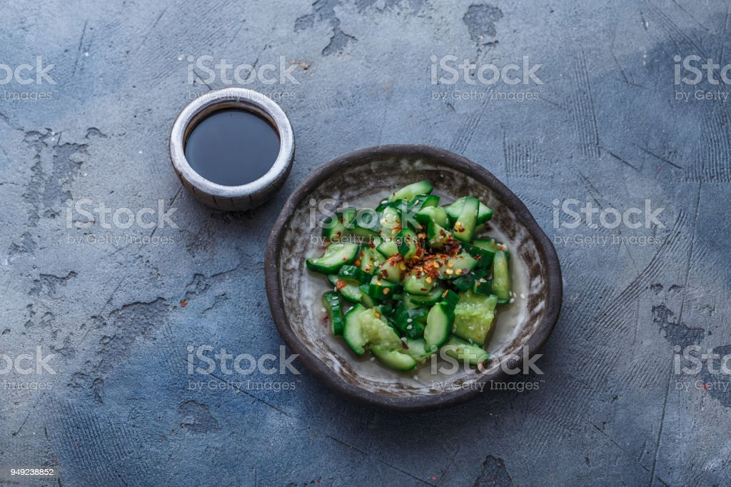Chinese beaten cucumbers salad, top view, dark background, place for text stock photo