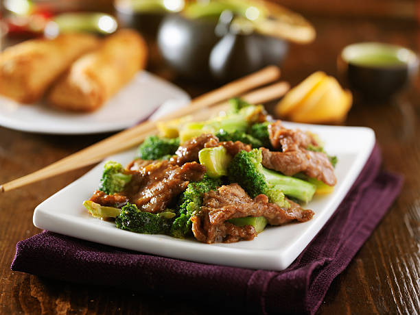 chinese beef and broccoli stir fry with sides stock photo
