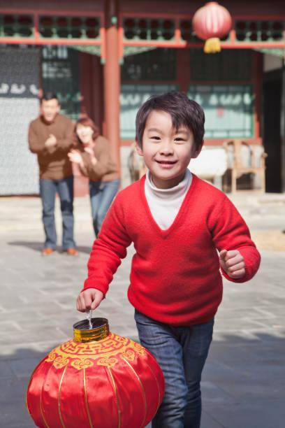 chinese boy carrying traditional lantern - festival delle lanterne cinesi foto e immagini stock