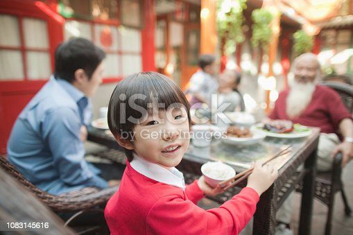 Chinese boy eating at table outdoors