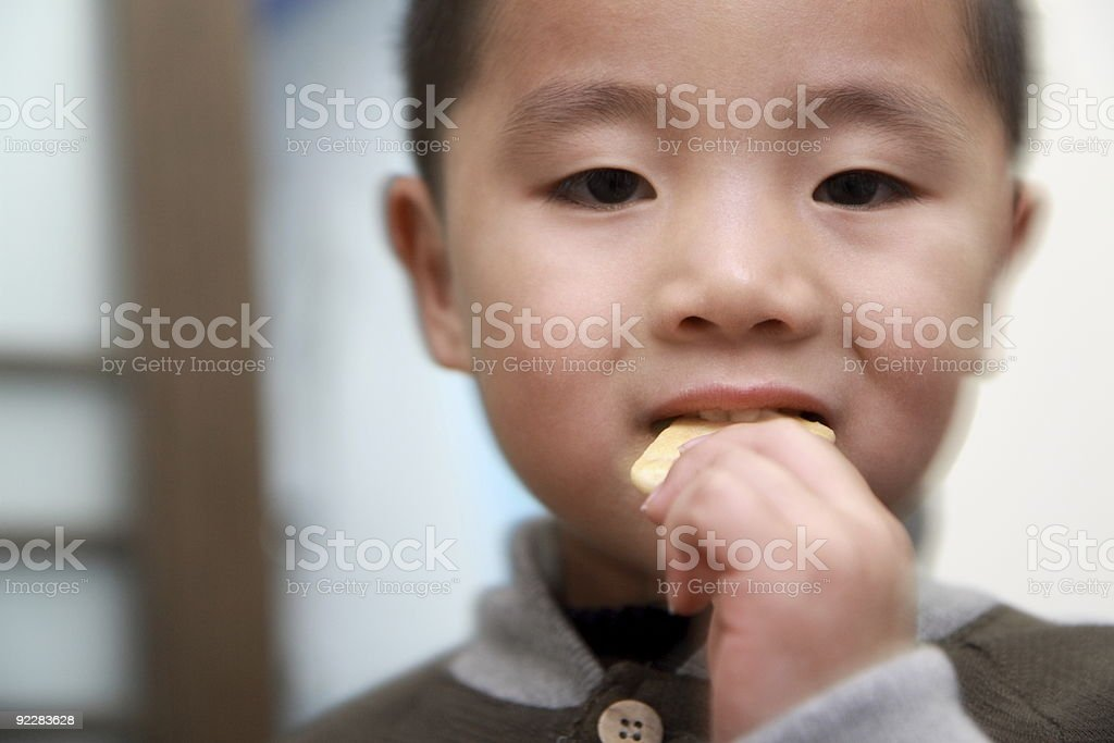 Chinese boy eating cracker royalty-free stock photo