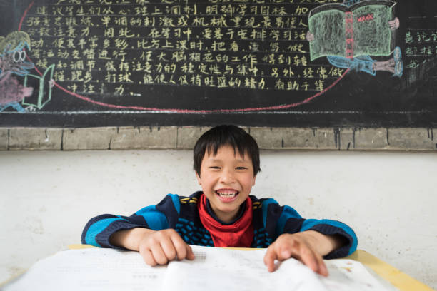 Chinese boy having fun at teachers desk in chinese school classroom stock photo