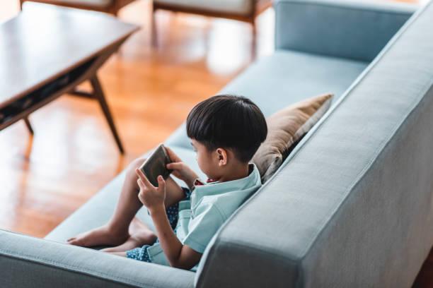 bocah cina menggunakan ponsel pintar di ruang tamu - child playing phone potret stok, foto, & gambar bebas royalti