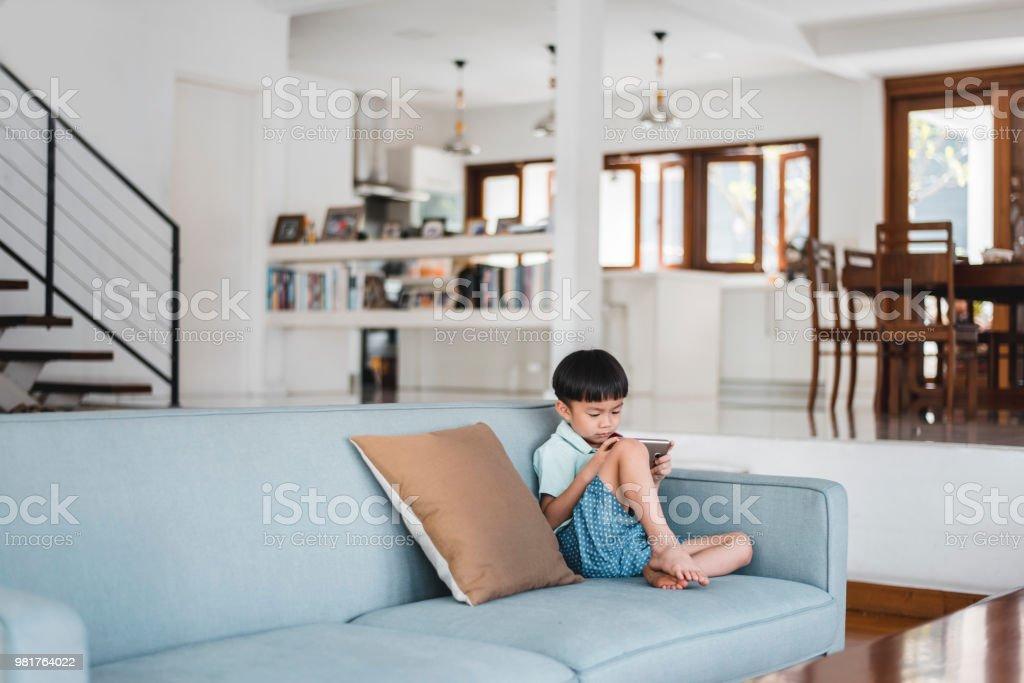 Chinesischen jungen mit Smartphone im Wohnzimmer – Foto