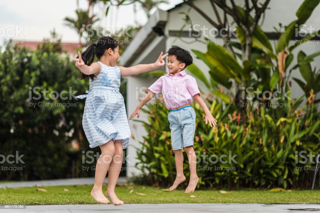 Chinese brother and sister jumping in the front yard Chinese brother and sister jumping in the front yard Bonding Stock Photo