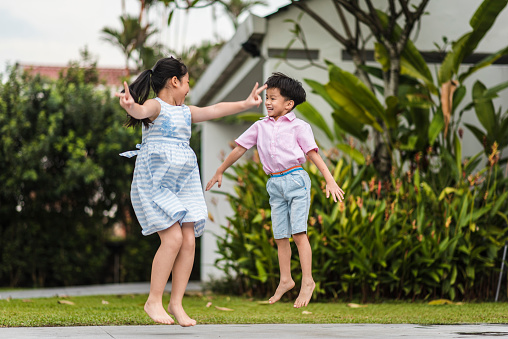Chinese Brother And Sister Jumping In The Front Yard Stock Photo - Download Image Now