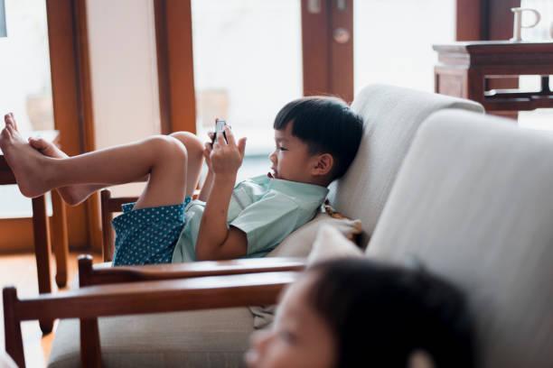saudara cina menggunakan ponsel pintar di ruang tamu - child playing phone potret stok, foto, & gambar bebas royalti