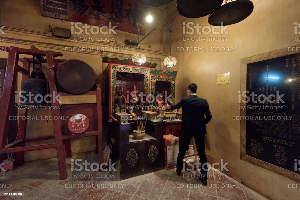 A Chinese Business Man at the Man Mo Temple in Hong Kong. stock photo