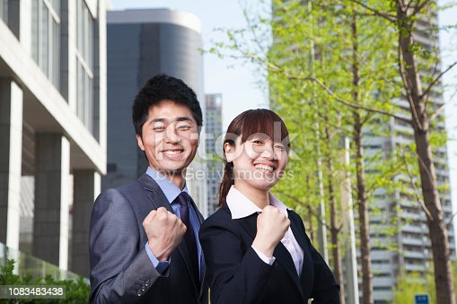 465474428 istock photo Chinese business people making fists outdoors 1083483438