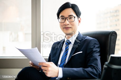960195072 istock photo Chinese business professional in office with paperwork 1200064747