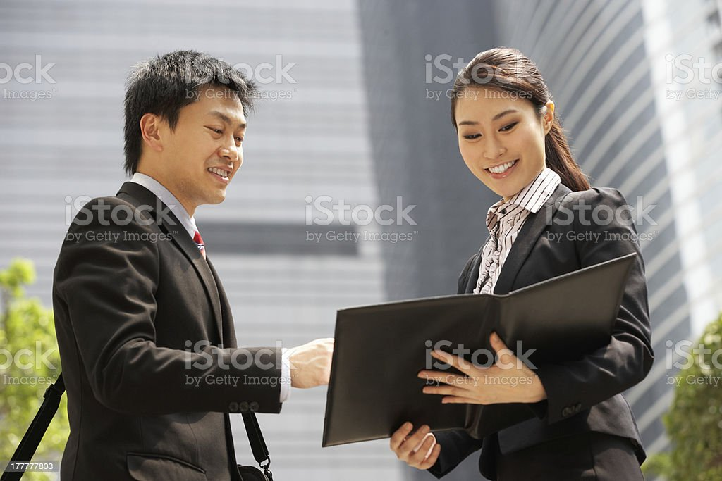 Chinese Businessman And Businesswoman Discussing Document Outsid royalty-free stock photo