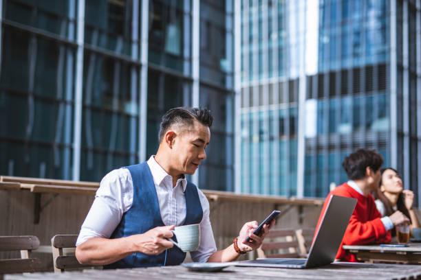 Chinesischer Geschäftsmann, der Kaffee trinkt und mit dem Smartphone in einem Café telefoniert – Foto