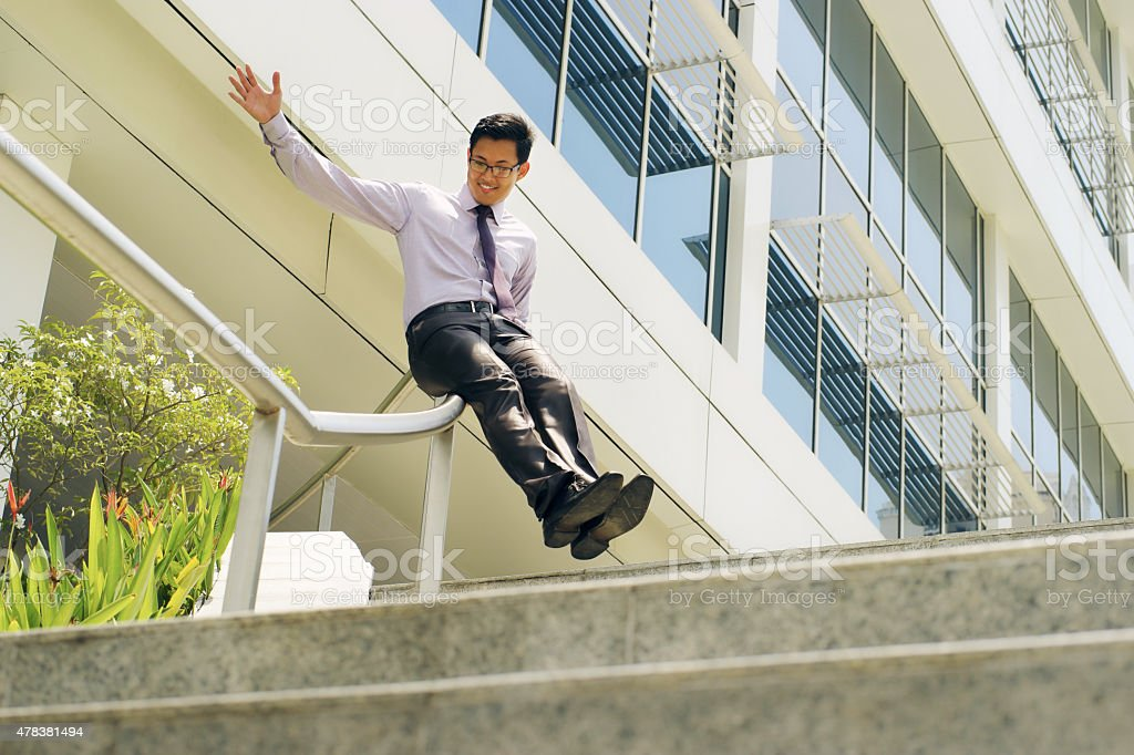 Chinese Businessman Going Downstairs Sliding On Rail For Joy stock photo