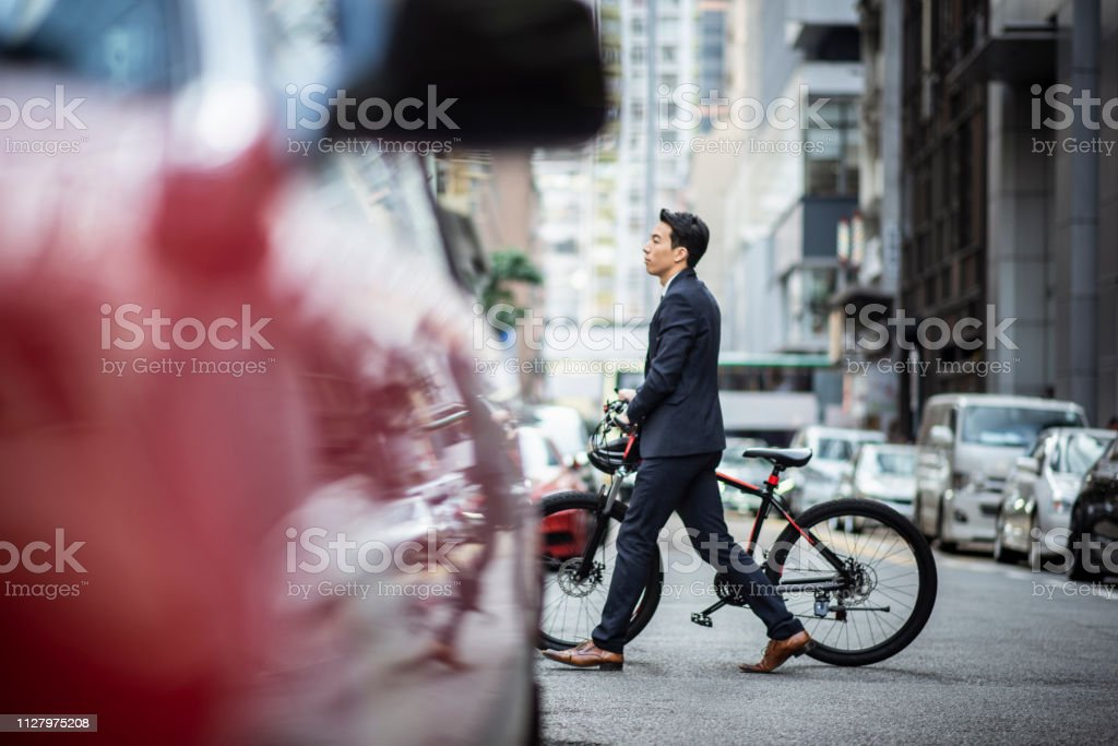 Chinese businessman going to work with his bicycle and crossing the...