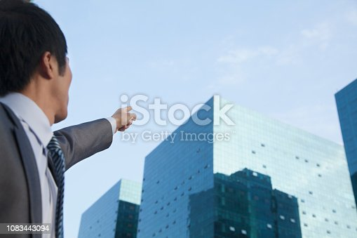 168589045 istock photo Chinese businessman pointing at high rise building 1083443094