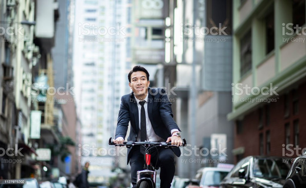 Chinese businessman riding to work with his bicycle