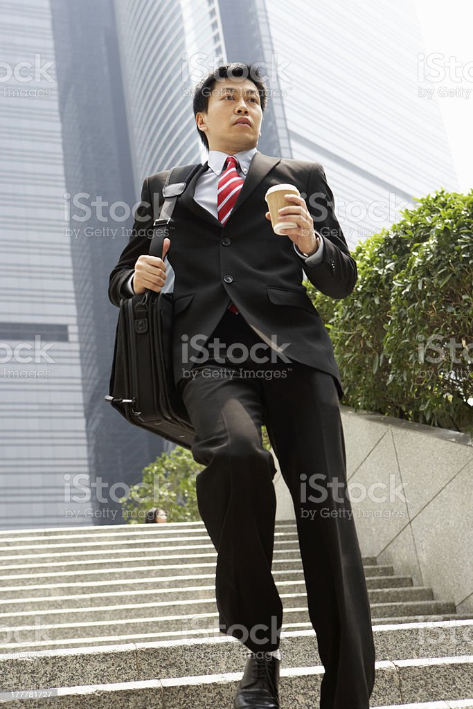 Chinese Businessman Rushing Down Steps Carrying Bag And Takeaway stock photo