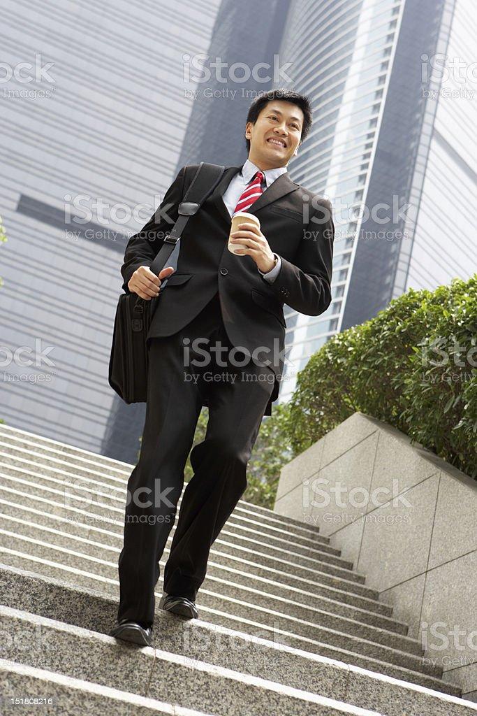 Chinese Businessman Rushing Down Steps stock photo
