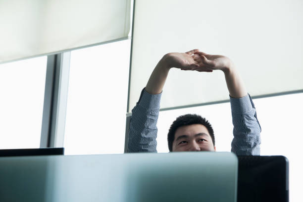 Chinese businessman stretching in office Chinese businessman stretching in office effortless stock pictures, royalty-free photos & images