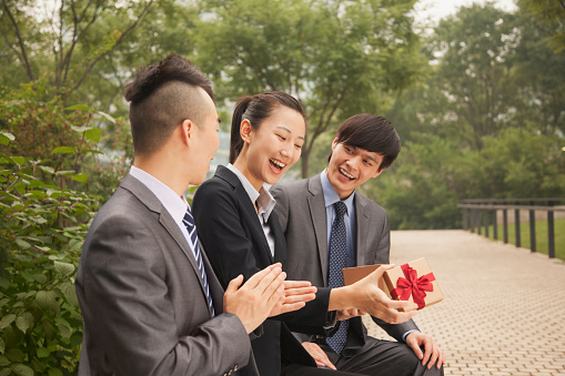 Chinese businessmen giving gift to colleague