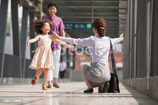 Chinese businesswoman greeting daughter on train platform