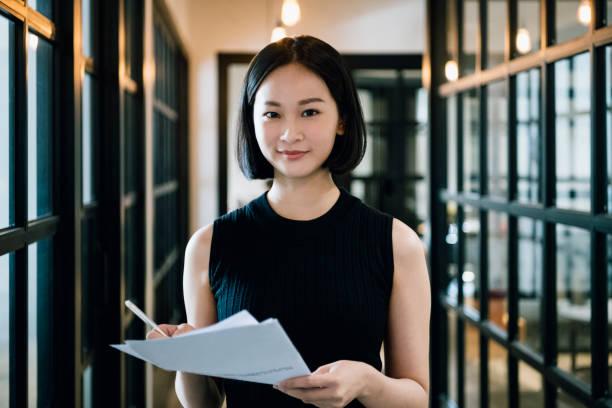 chinese zakenvrouw in haar jaren ' 30 holding papierwerk en glimlachen - mid volwassen vrouw stockfoto's en -beelden