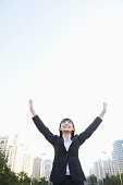 Chinese businesswoman in urban park with arms raised