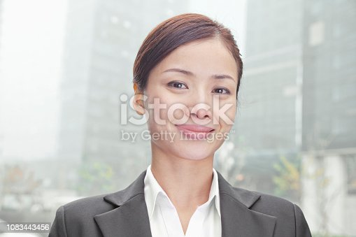 istock Chinese businesswoman smiling and looking at camera 1083443456
