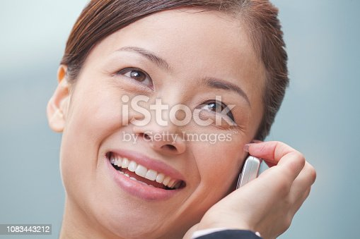 istock Chinese businesswoman talking on cell phone close up 1083443212