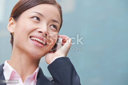 istock Chinese businesswoman talking on cell phone outside 1083443358