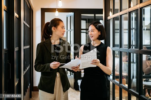 Two attractive female colleagues sharing notes between meetings, confidence, success, support