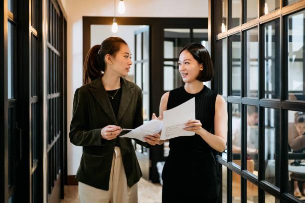 Chinesische Geschäftsfrauen diskutieren im Flur – Foto