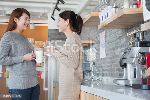 Chinese businesswomen having coffee break in office kitchen