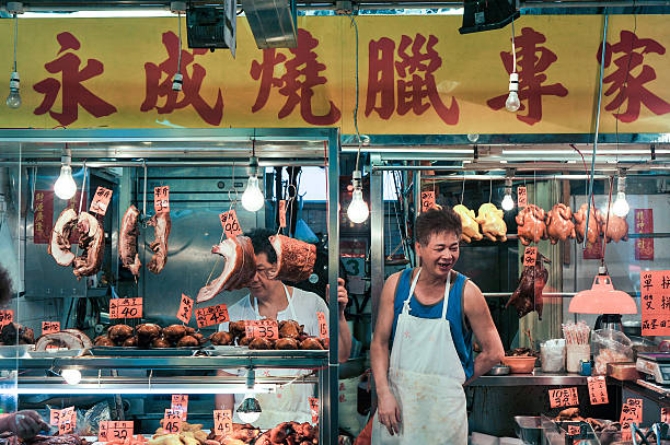 Chinese Butcher at his shop in the market stock photo