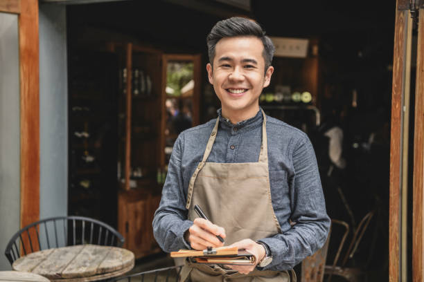 Chinese cafe manager wearing apron by cafe Cheerful waiter smiling at camera, in front of restaurant, holding pen and notepad, service, efficiency, welcoming waiter stock pictures, royalty-free photos & images