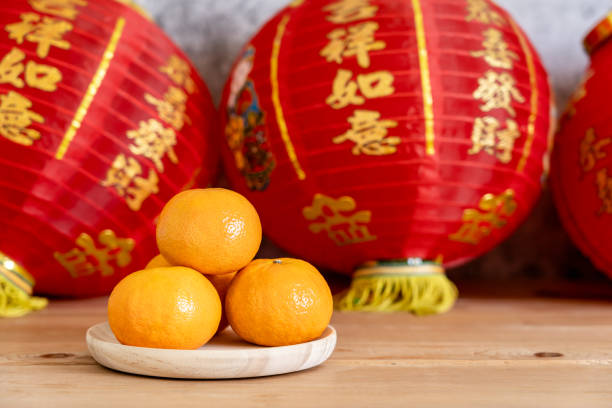 Chinese character means fortune and luck.Accessories on Lunar New Year & Chinese New Year vacation concept holiday background.Orange in wood basket and red lantern on brown wooden & grey stone. stock photo