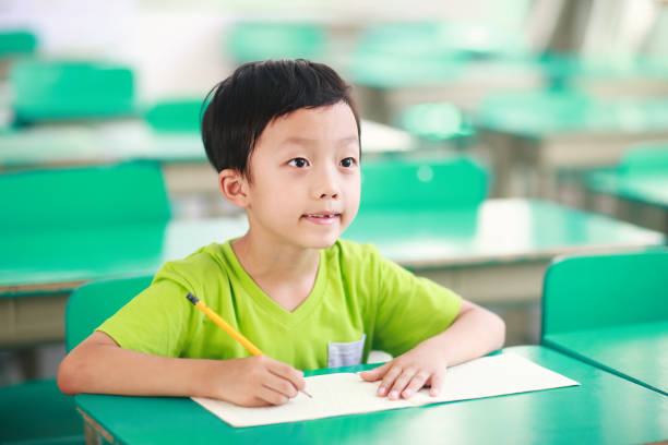 Chinese children working at desks in their classroom stock photo