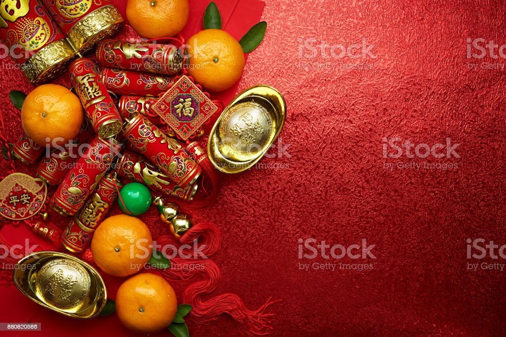 運や中国の結び目と中国ゴールドインゴットと伝統的な中国の結び目 (祝福外国のテキストを意味します) と赤い封筒と赤い背景の上に新鮮なオレンジが付いている装飾の中国の硬貨 ストックフォト