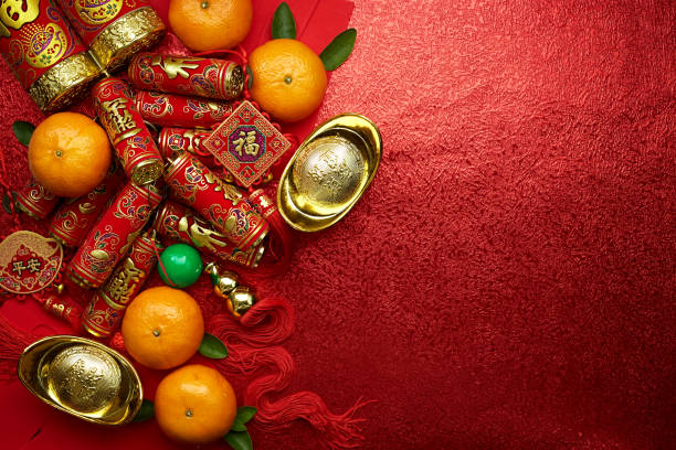 Chinese coins of luck or chinese knot and Chinese gold ingots and Traditional chinese knot  (Foreign text means blessing) and Red envelopes and decoration with Fresh oranges on Red background stock photo