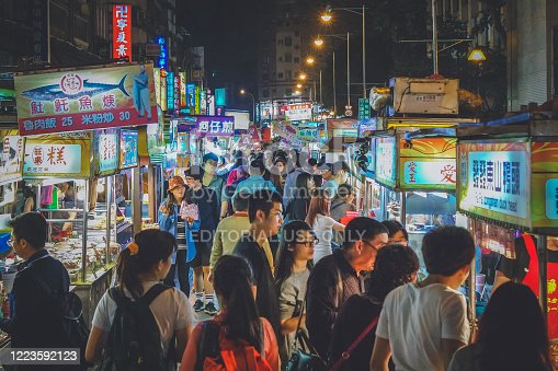 Chinese commuters walk together in a densely populated local night street market. There are little stalls left and right down the alley.